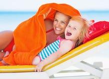 Mère heureuse et bébé s'étendant sur la chaise longue et regardant sur la cannette de fil Photographie stock libre de droits