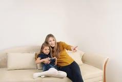 Mère heureuse et doughter détendant et jouant des jeux de TV sur le s Photographie stock libre de droits