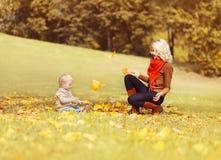Mère heureuse et enfant jouant ainsi que les feuilles jaunes sur l'herbe ayant l'amusement dans le parc d'automne photo libre de droits