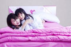 Mère heureuse et enfant se trouvant sur le lit image libre de droits