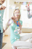 Mère heureuse et enfants jouant avec des baguettes magiques de bulle à la maison Image stock
