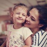 Mère heureuse et fille appréciante mignonne caressant avec amour d'intérieur C Photo stock