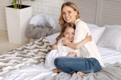 Mère heureuse et fille caressant sur le lit Images stock