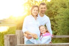 Mère heureuse et fille de père de famille détendant en parc Images stock