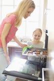 Mère heureuse et fille enlevant le plateau de biscuit du four à la maison photographie stock libre de droits