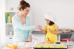 Mère heureuse et fille faisant cuire au four à la maison Photo stock