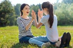 Mère heureuse et fille jouant le Pat-un-gâteau en parc Photos libres de droits