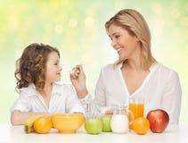 Mère heureuse et fille mangeant le petit déjeuner sain Photographie stock libre de droits