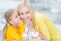 Mère heureuse et fille s'asseyant dans le café Photo stock