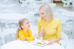 Mère heureuse et fille s'asseyant dans le café Image stock