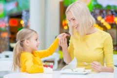 Mère heureuse et fille s'asseyant dans le café Photographie stock libre de droits