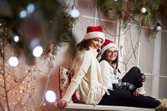 Mère heureuse et fille s'asseyant sur un rebord de fenêtre sur Noël e Photos stock