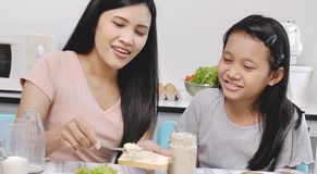 Mère heureuse et fille souries faisant des sandwichs images stock