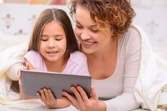 Mère heureuse et fille surfant l'Internet Photos stock