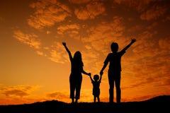 Mère heureuse et fils de père de famille jouant dehors au coucher du soleil SI Images stock