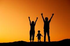 Mère heureuse et fils de père de famille jouant dehors au coucher du soleil SI Photos libres de droits