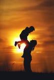 Mère heureuse et fils jouant contre le coucher de soleil photographie stock libre de droits