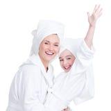 Mère heureuse et jeune fille dans la robe de chambre blanche Photographie stock libre de droits