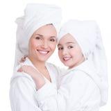 Mère heureuse et jeune fille dans la robe de chambre blanche Photographie stock
