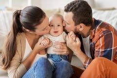 Mère heureuse et père embrassant le bébé à la maison Photos libres de droits