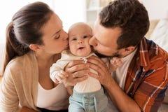 Mère heureuse et père embrassant le bébé à la maison Photographie stock