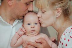 Mère heureuse et père embrassant le bébé Photographie stock libre de droits
