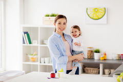 Mère heureuse et petite cuisine de bébé à la maison Photos libres de droits