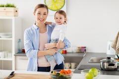 Mère heureuse et petite cuisine de bébé à la maison Image libre de droits