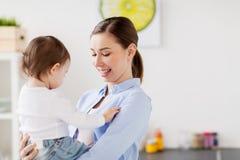 Mère heureuse et petite cuisine de bébé à la maison Photos stock