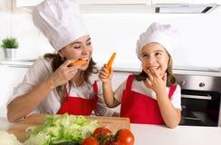 Mère heureuse et petite fille dans le chapeau de tablier et de cuisinier mangeant des carottes ayant ensemble la cuisine d'amusem Images stock