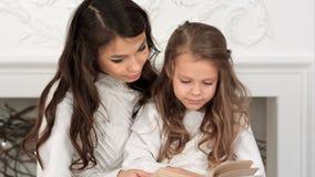 Mère heureuse et sa belle fille dans des chandails blancs lisant un livre le réveillon de Noël Photos libres de droits