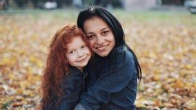 Mère heureuse et sa fille examinant la position de caméra en parc d'automne Filles souriant et riant Mouvement lent clips vidéos