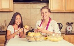 Mère heureuse et souriante et fille faisant cuire le dîner Photos stock