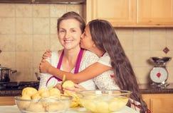 Mère heureuse et souriante et fille faisant cuire le dîner, préparant la nourriture Images stock