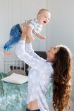 Mère heureuse jouant avec le bébé Photos stock
