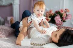 Mère heureuse jouant avec le bébé garçon se trouvant sur le lit à la maison Photo stock