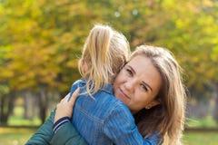Mère heureuse jouant avec sa fille l'étreignant en parc photo libre de droits