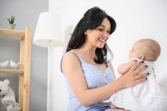 Mère heureuse jouant avec son bébé à la maison photos libres de droits