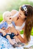 Mère heureuse jouant avec son fils, qui a des cerveaux Images stock