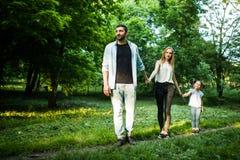 Mère heureuse, père et petite fille marchant en parc d'été et ayant l'amusement Image stock