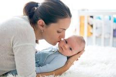 Mère heureuse, parlant à son fils nouveau-né, frottant et embrassant h image libre de droits