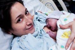 Mère heureuse retenant la chéri nouveau-née après naissance
