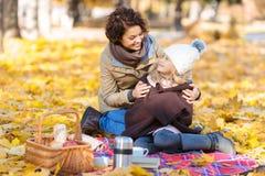 Mère heureuse s'asseyant sur la couverture avec elle Photographie stock libre de droits