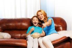 Mère heureuse se dirigeant à rire de TV et de fils Photographie stock