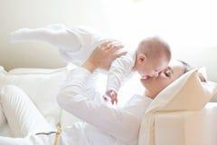 Mère heureuse tenant son beau bébé de sourire Photos stock