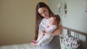 Mère heureuse tenant un bébé nouveau-né dans des ses bras banque de vidéos