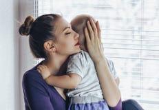 Mère heureuse tendre de jeunes étreignant son se reposer de sourire de bébé nouveau-né sur le rebord de fenêtre dans le matin App photos libres de droits