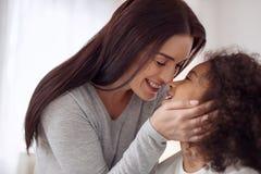 Mère inspirée embrassant sa petite fille Photos stock