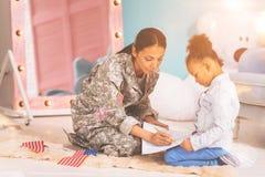 Mère inspirée montrant à sa fille comment dessiner Photos stock