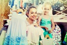 Mère intéressée avec les enfants de achat de fille vêtements Photographie stock